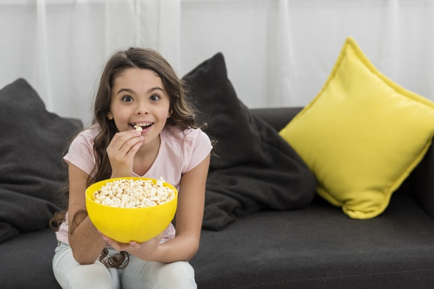 little-girl-eating-popcorn-couch_23-2148396091